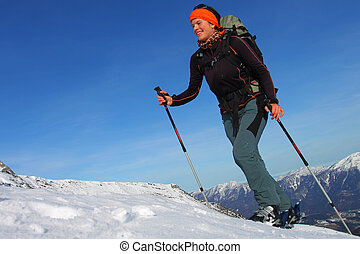 Smiling woman doing ski touring. Outdoor winter activity
