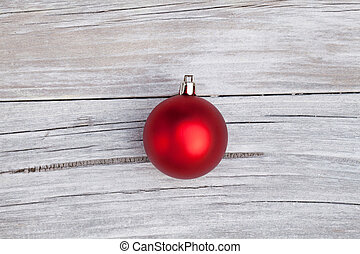Red christmas bulb on rustic wood