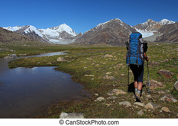 Trekker with backpack in Pamir, Tajikistan, Central Asia