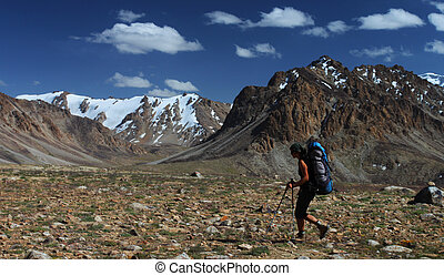Hiker with backpack in mountains of Central Asia, Pamir,...