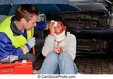 Accident on a rainy day - Paramedic caring for an injured...