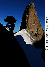 Mountain sport - silhouette of a climber with rocky pinnacle...