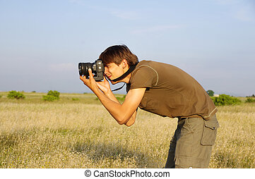 The photographer behind work in an open field