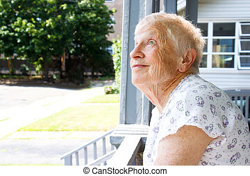 Happy senior lady relaxing in porch