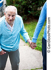 Senior lady walking with caregiver, holding hands