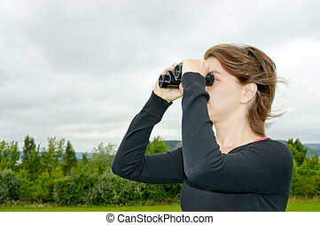 Woman with binoculars - A young woman searching something...