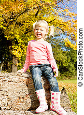 little girl sitting in autumnal nature