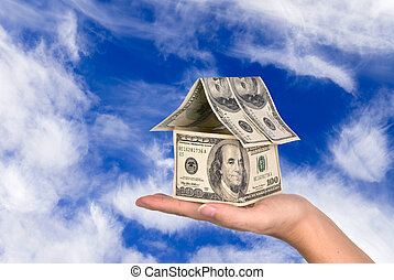 Money house held against the sky - A conceptual real estate...