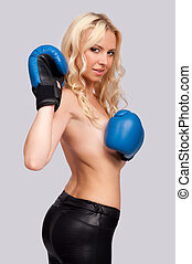 a woman with a bare chest with boxing gloves