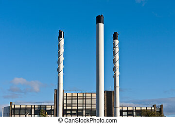 Chimney stacks - Industrial chimney stacks against a clear...