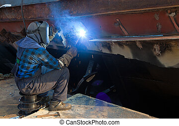 Welder in a protective mask when working. Photo taken on:...