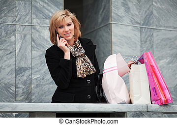 Young blond shopper on the phone agaist of store wall