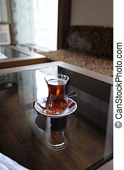 A glass of Turkish tea with a spoon