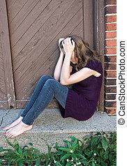 lonely teenage girl - Teenage girl huddled in old doorway.