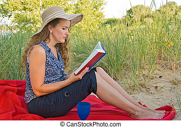 woman reading a book - Young woman reading a book on a red...