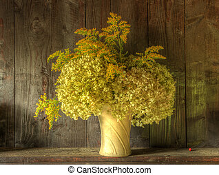 Still life image of dried flowers in rustic vase against...