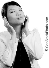 Woman listening to music through head phones - Attractive...