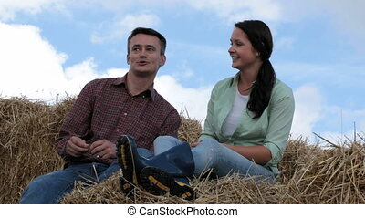 Couple on haystack - Husband and wife sitting on haystack...