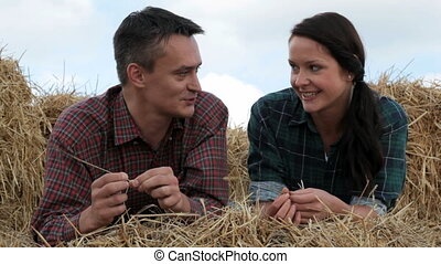 Relaxing on haystack - Couple lying on haystack and...