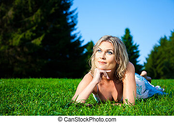 Portrait of attractive woman in blue sundress lying on green...