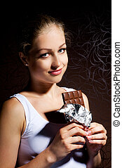 pretty young girl eating chocolate on a dark background
