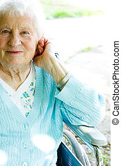 Beautiful senior lady in wheelchair in spring day