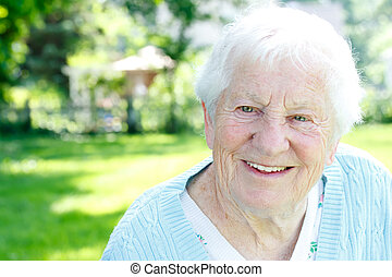 Happy senior lady smiling in spring garden