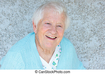 Happy senior lady smiling in front of light blue wall