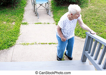 Senior lady standing in front of staircase and holding...
