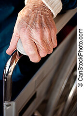 Senior woman\'s hand on a wheelchair - Senior woman holding...