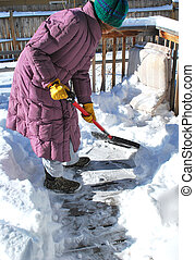 Winter snow. - Female shoveling snow off her patio deck.