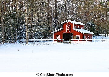 A snow covered Horse barn in a field in the woods covered in...