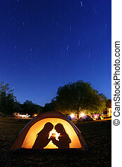 Children Camping at Night in a Tent With Star Trails