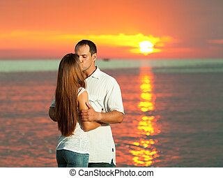 Sunrise kiss - Young couple kissing near the sea at sunrise