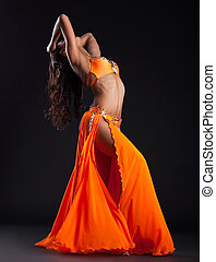 Expressive woman posing in orange arabic costume