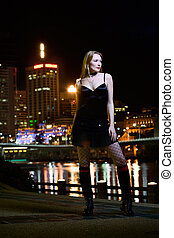 Nightlife - Beautiful young lady waits by the riverside at...