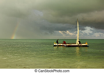 men on a pirogue, calm oily sea, rainbow and storm in the...