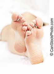 Bare relaxed feet - Soles of soft female bare feet crossed...