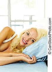 Smiling woman in bed in the morning - Happy blonde woman...
