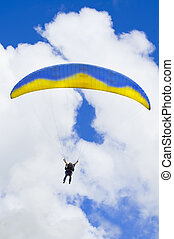 Parachuter descending against blue sky - Parachuter...