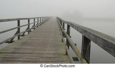 mist on lake bridge and bicyclist