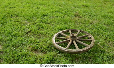 carriage wheels on the grass - two old carriage wheels on...