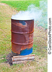 Burning Barrel - A burn barrel burning a pile of trash with...