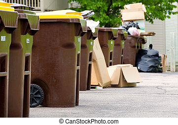 Garbage Day - A Group of Garbage Cans in a Row with Garbage...