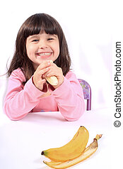 Little girl eating banana - Young little girl smiling eating...