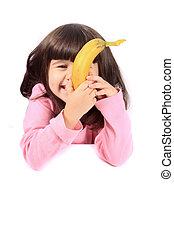 Little girl eating banana - Young little girl hiding her...
