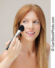 happy woman applying blusher with brush - happy young woman...