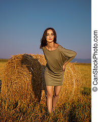 beautiful woman leaning hay stack enjoying breeze - young...