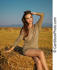 young woman enjoying summer breeze hay stack - beautiful...