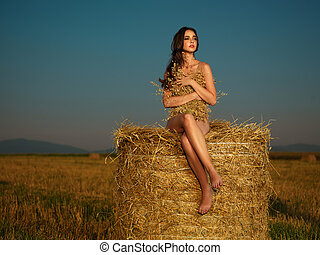 young woman watching sunset on hay stack - beautiful nude...